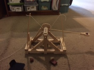 A wooden catapult model with cargo swinging. Copyright 2015 Andrea LeDew