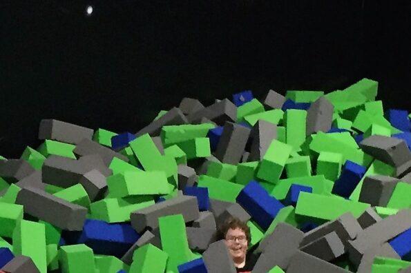 A happy kid in a pile of foam rubber blocks in a trampoline bouce house.  By Andrea LeDew.