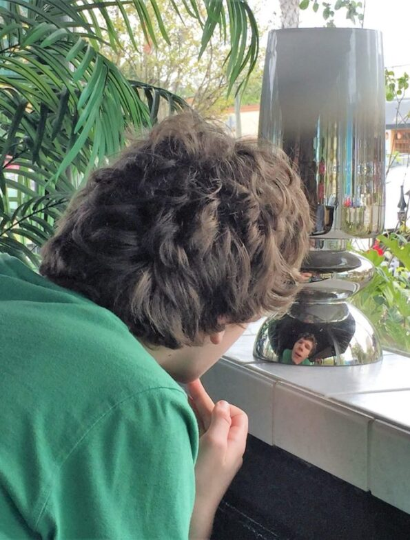A teenager contemplating his own image in a rounded chrome lamp base. Copyright Andrea LeDew.