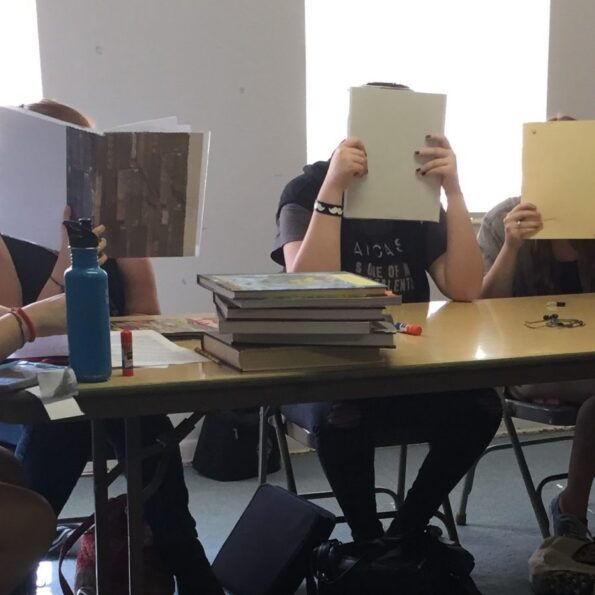 Teenagers at a folding table, hiding their faces behind their books.  Copyright Andrea LeDew