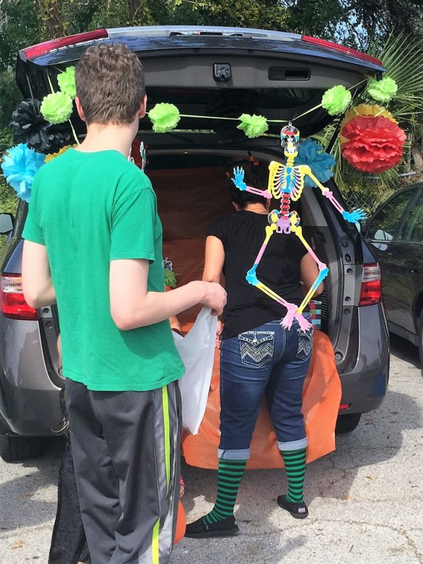 Teen boy waiting for candy from a Trunk or Treat van decorated with Day of the Dead imagery.  Copyright Andrea LeDew