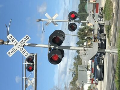 A railroad crossing flashing red. By Andrea LeDew.
