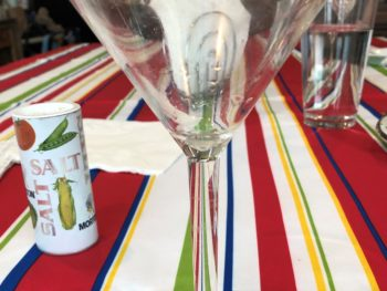 Empty martini glass on on striped colorful tablecloth, with the stem taking on the stripes of the tablecloth, and a saltshaker,water glass and napkin holder on the the table behind it. Copyright Andrea LeDew