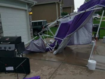 A purple party tent in tatters in a driveway with a garage in background and a barbecue grill in the foreground, in suburban neighborhood.PHOTO PROMPT © Jan Wayne Fields