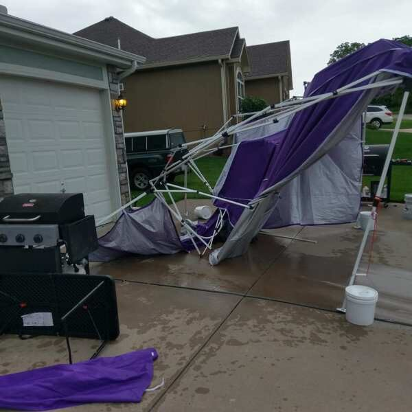 A purple party tent in tatters in a driveway, with a garage in background, and a barbecue grill and a tipped table in the foreground, in suburban neighborhood.PHOTO PROMPT © Jan Wayne Fields