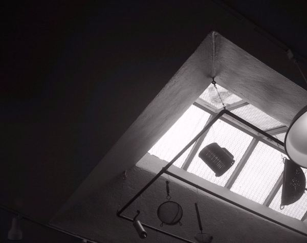 A black and white image of a window in the ceiling, with objects hung or suspended on a rack in front of it so that the light shows them as shadows. Among the objects is a beer stein, or perhaps it is a flour sifter.PHOTO PROMPT © J Hardy Carroll