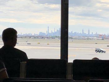 Silhouette of a passenger, waiting at Newark NJ Airport, and looking out the window over the tarmac, to the skyline beyond. Copyright Andrea LeDew.