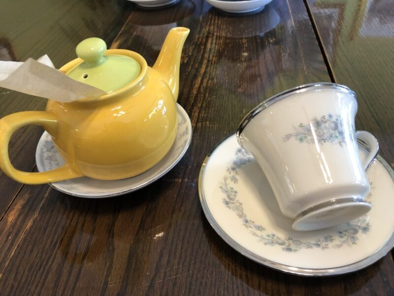 A yellow teapot and a tipped teacup both on saucers. Copyright Andrea LeDew