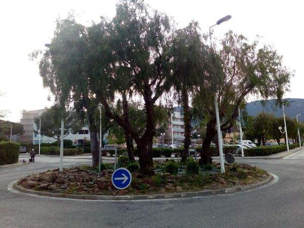 Intersection with a roundabout or traffic circle, in the center, planted with trees and bushes that look like they could be human forms, crouching around a fire. Copyright CE Ayr