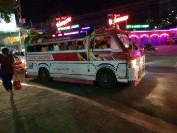 Minibus filled with people in a neon-lit area of town at night. PHOTO PROMPT © Fatima Fakier Deria