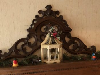 Ornate fireplace mantel with small empty wooden birdcase in the center and two wooden painted birds perched on either side. Copyright 2020 Andrea LeDew