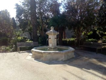 Stone fountain with a sitting bench around it holding a pool of water . Copyright CE Ayr