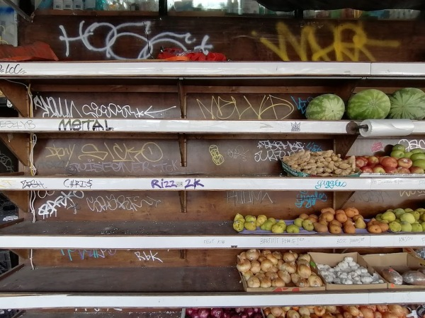 Metal shelves behind the counter at a farmer's market, covered in graffiti holding various fruits and vegetables. Copyright Roger Bultot