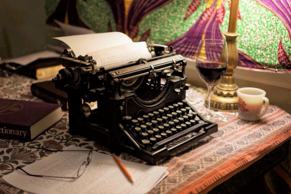 A black old-style manual typewriter, with paper already in it, poised on a cloth covered desk with a glass of wine and a mug of coffee. Photo by Jeff Arnold.