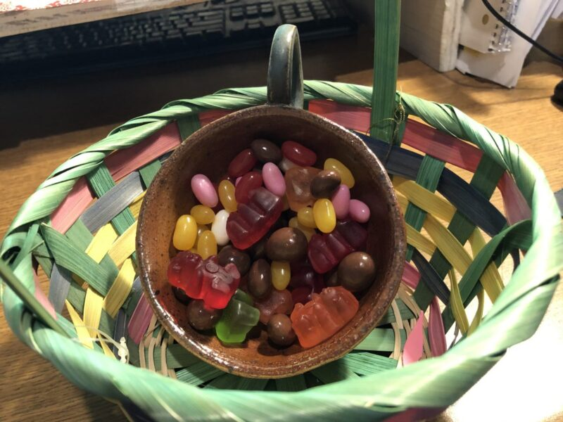 An assortment of jellybeans and gummy bears in a teacup, inside an Easter basket. Copyright Andrea LeDew