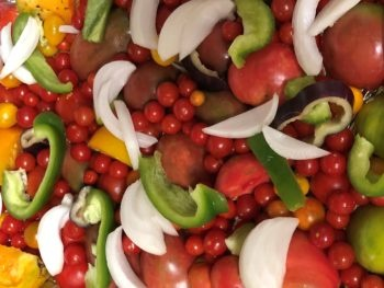 Tomatoes, peppers and onions from a home garden, laid out on a baking sheet, ready to roast. Copyright Andrea LeDew