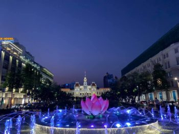 A long view down a promenade, with a fountain capped with a pink lotus in the central foreground, and a fancy building at the end of the avenue. PHOTO PROMPT © David Stewart