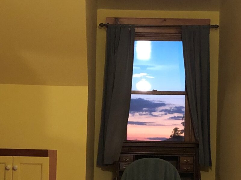 A sunset seen through a second floor window in a yellow room. Copyright ANdrea LeDew.