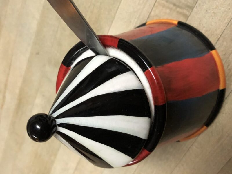A sugar bowl in the shape of a circus tent, with a spoon stuck under the lid, on a butcher-block counter. Copyright Andrea LeDew.