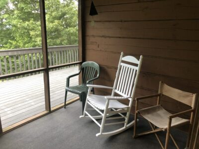 Three chairs on a screen porch, unoccupied. Copyright Andrea LeDew.