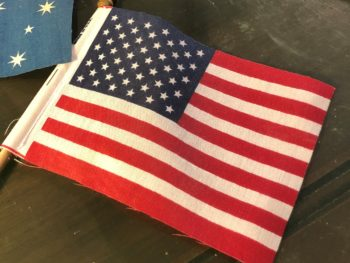 A small cloth American flag next to a bit of an Australian flag. By Andrea LeDew.