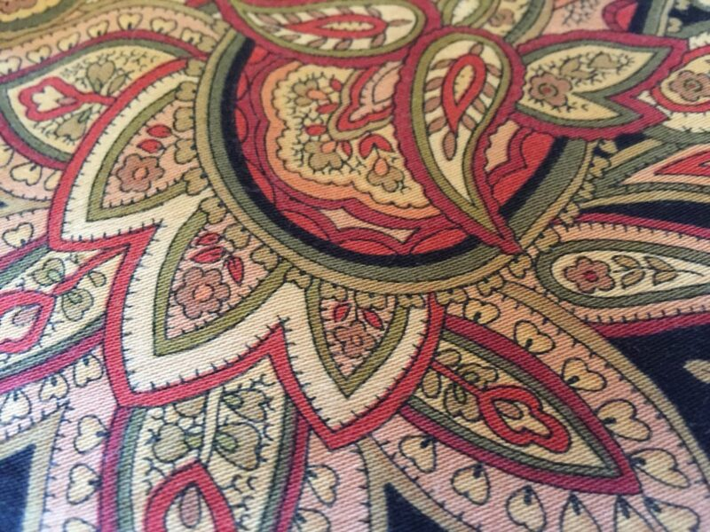 A snippet of a paisley tablecloth, on which there are hardly any straight lines.