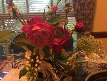 A bouquet of roses and cat's whiskers on a kitchen table before a window with open blinds and the side panel of a curtain. Copyright 2020 Andrea LeDew.