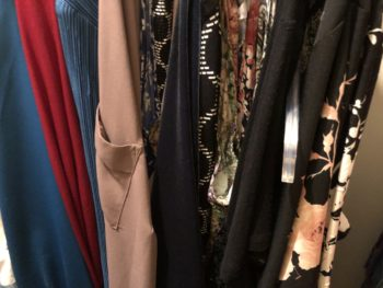 Various blouses hanging on a rack in a closet. By Andrea LeDew.
