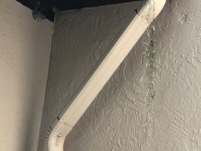 A downspout which has come unattached, for lack of the proper attention being paid to it. By Andrea LeDew.