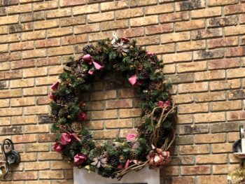 Large decorated wreath on a brick fireplace wall flanked by two candle sconces. Copyright Andrea LeDew.