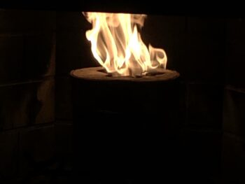 A thick upended hollowed-out log burning rapidly in a fireplace with all surrounding it flung into darkness. Copyright Andrea LeDew.