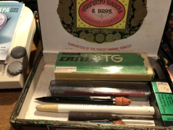 Various writing implements in an open cigar box. By Andrea LeDew.