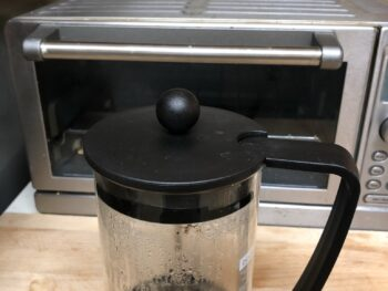 Empty French press coffee pitcher on wooden cutting board in front of toaster oven Copyright Andrea LeDew.