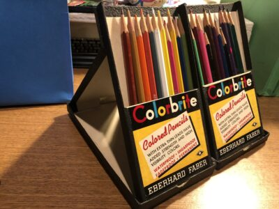 Old pack of colored pencils standing upright in a case. By Andrea LeDew