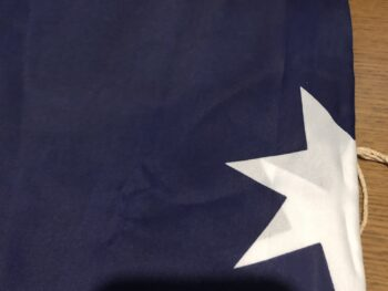 A folded Australian flag showing only a field of blue and a large white star folded in half. Copyright Andrea LeDew.