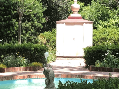 A cherub fountain in the middle of a small, blue pool, with a pedestal beyond, surrounded by greenery. Copyright Andrea LeDew.