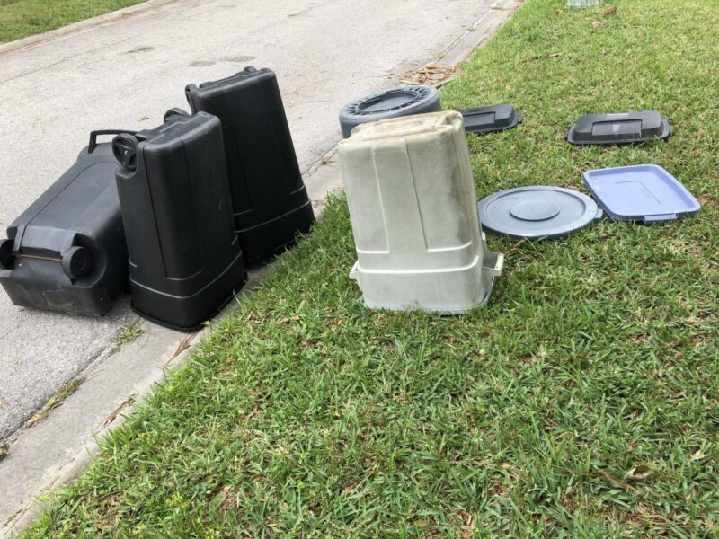 Trash cans tipped upside down and sideways at the edge of the road after the garbage truck has come. Copyright Andrea LeDew.