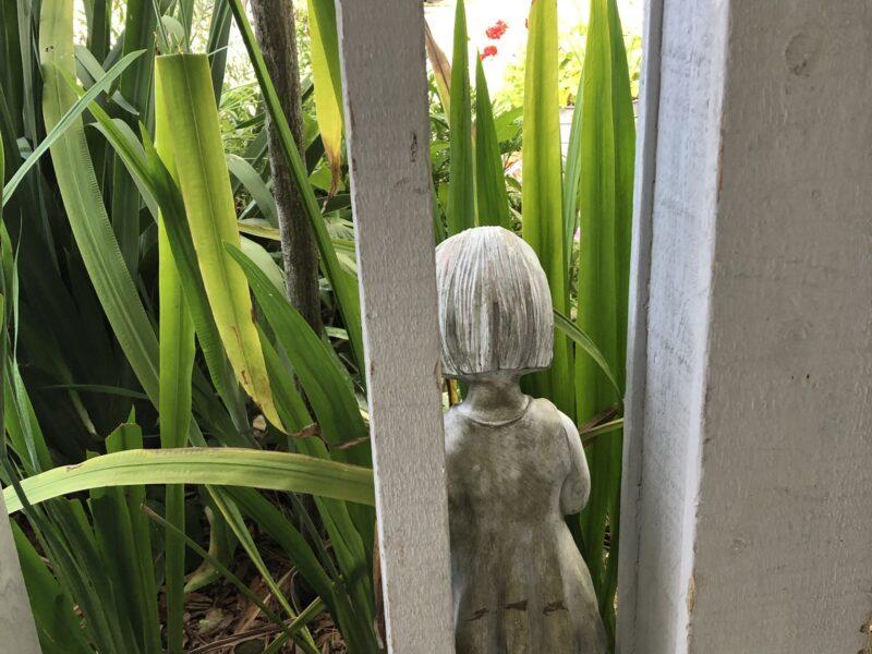 Little girl statue, facing away, among tall iris leaves, seen through a porch balustrade. Copyright Andrea LeDew.