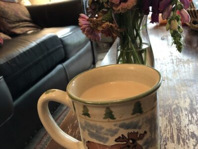 A full coffee mug of heavily-creamed coffee, sitting on a coffee table. Copyright Andrea LeDew.before a vase of flowers