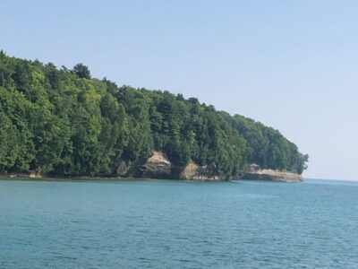 Forests above painted rocks on the shores of Lake Superior near Munising, Michigan.