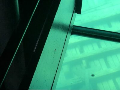 A pacifier, on a clear pane of a glass-bottom boat, as it glides over a shipwreck. Copyright Andrea LeDew.