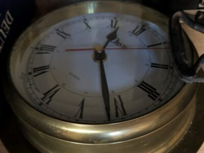 A brass clock, laid flat on a shelf, as if by someone not interested in timeliness. Copyright Andrea LeDew.