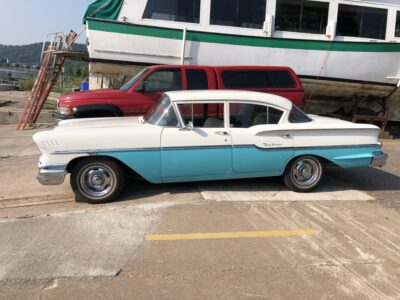 A beautiful 1950's white-topped Chevrolet Delray with turquoise trim, parked near Lake Superior in Munising, Michigan. Copyright Andrea LeDew.