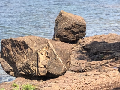 A bleak and harshly beautiful prospect from the shore of Lake Superior, with stacked boulders before a wide expanse of lake. Copyright Andrea LeDew